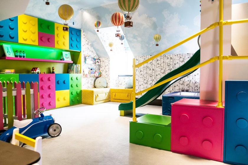 Lego themed playroom_Londons Colourful PLayroom_Angled walls and sloping ceiling kids room design_MK Kids Interiors_pink-green-blue-yellow and white kids playroom_playroom designer